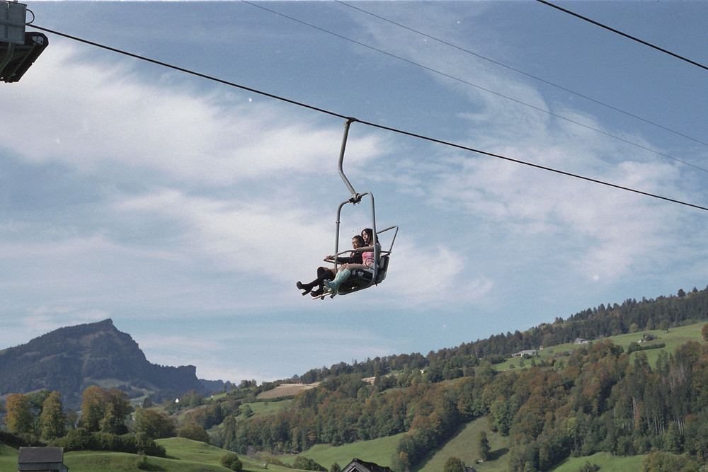 Two people soar above a lush green landscape in a ski lift. The sky behind them is blue with gentle tendrils of cloud.