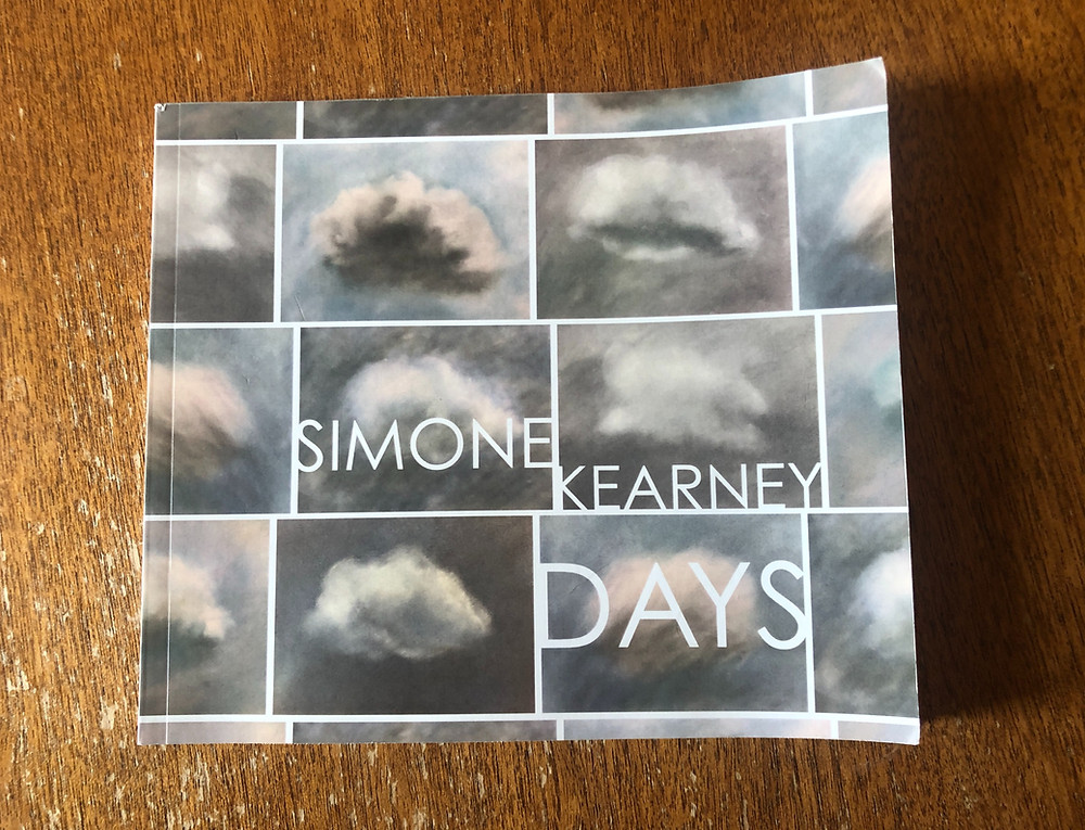 A rectangular book called 'Days' by Simone Kearney lies on wood. The cover of the book displays a number of different clouds, which look as though they have been created using charcoal and chalk pastels.
