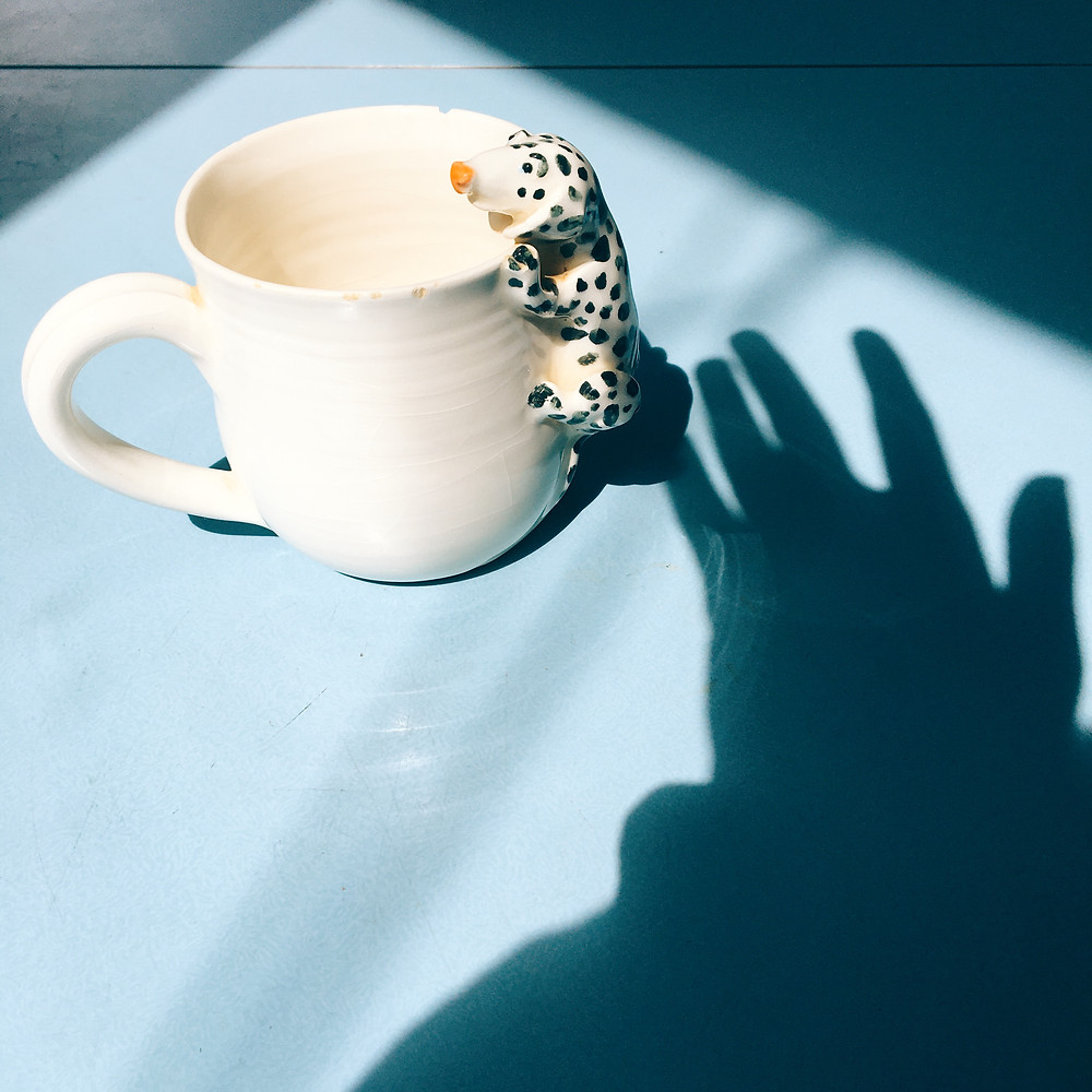 The shadow of a hand hovers near a chipped mug with a ceramic Dalmatian hanging off the side. The cup is on a pale blue formica table.