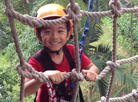 Small smiling asian child on ropes.png