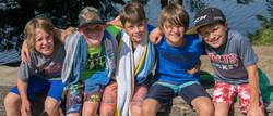 4 boys arms over shoulders smiling.jpg