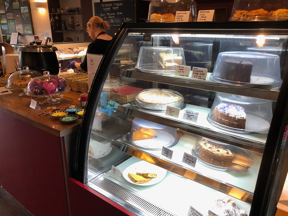 Counter with cake display at Aroma, with member of staff in the background preparing food.