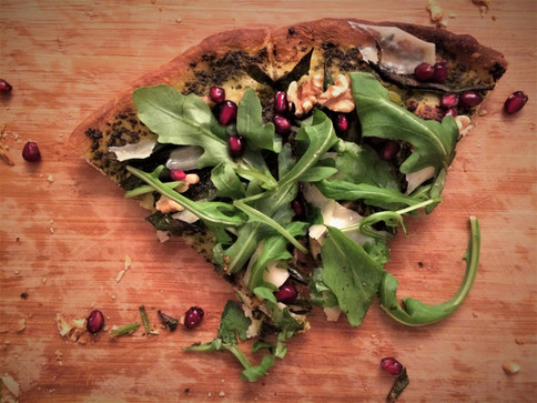 green pizza with basil pesto, green beans, rocket, walnuts and pomegranate, shavings of parmigiano