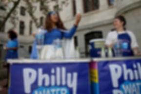 Water Woman stands in from of a Philly Water Bar table, proudly holding a glass of water and pitcher. She is wearing a blue and white cape, blue top, and white skirt. She is also wearing a blue headband, which holds back shoulder-length brown hair.