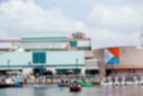 Independence Seaport Museum building in background with water and rowboats in foreground. People interspersed. It is sunny and partly cloudy..