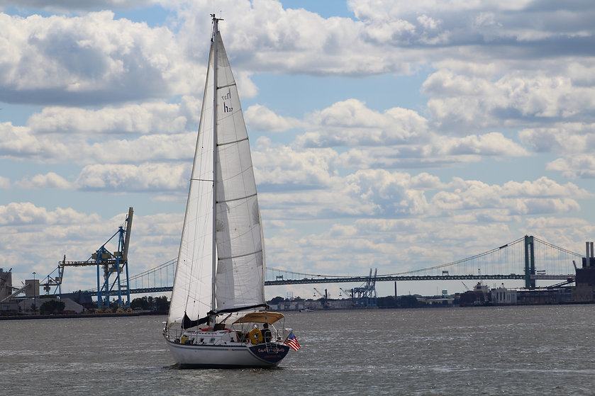 Photo of a sailboat on the water in a more industrial part of the city. A bridge is in the background, along with industrial crane equipment. It is a partly-cloudy day.