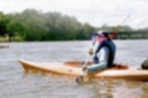 Photo of smiling person wearing a blue life jacket and bale-blue long sleeved shirt in bright orange kayak on the river. They have a paddle in their hands and are smiling at the camera. There are trees in the background.