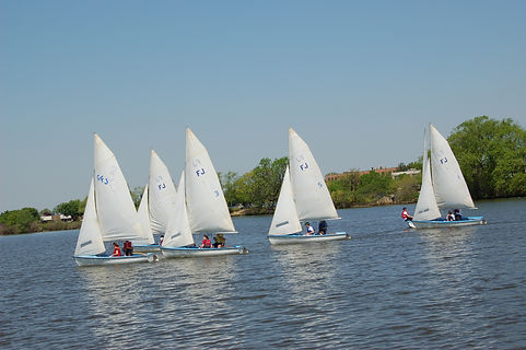 Photo of white sailboats on a body of water with trees in the background. There are people wearing life vests in the boats and it is a nice, sunny day.
