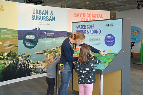 Snapshot of the Rivers Alive! exhibit at the independence seaport museum featuring a white woman and two young children in front of the Water Goes Round & Round exhibit.