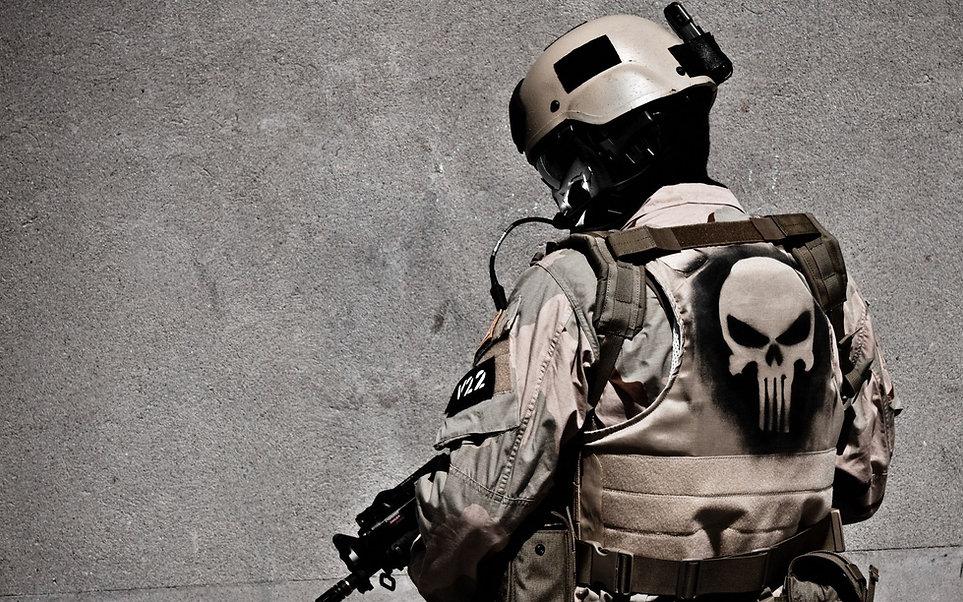 Soldado de costas com uma caveira desenhada nas costas do seu colete à prova de balas.