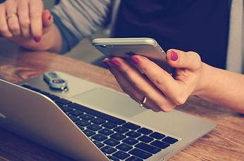 Frau mit Handy und Computer.jpg