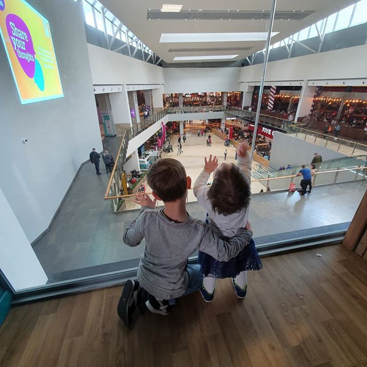 child and baby looking down a glass wall into the shopping mall below