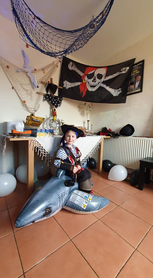 Joseph sitting in an inflatable shark with a pirate flag above him