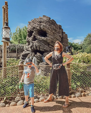 Me and my son standing in front of Skull Rock at Disneyland Paris. I'm wearing a Mickey Mouse bum bag from EMP (use my discount)