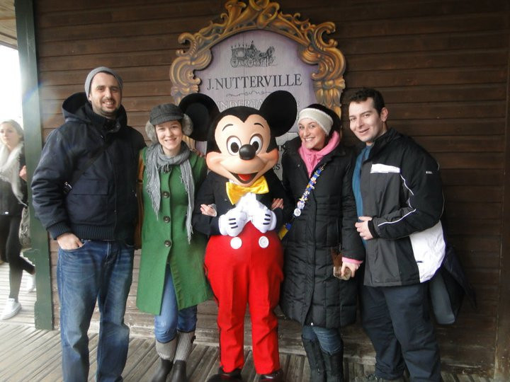 Leah and I and our husbands taking a photo with Mickey
