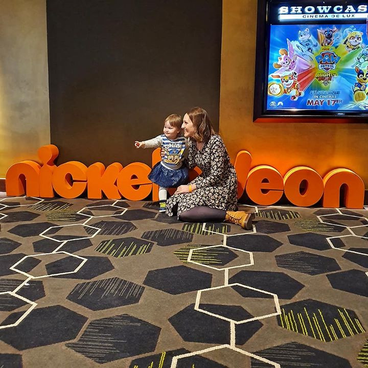 me and baby sitting on the floor in front of a sign that says Nickelodeon