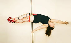 Woman in plank position on a pole
