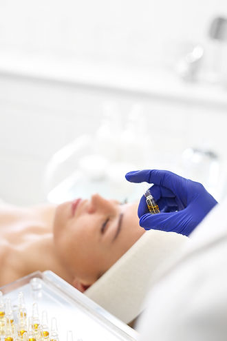 Chemical peeling, exfoliating treatment. Beautician imposes on the woman's face a cosmetic