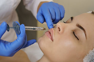 Aesthetic cosmetology. Lip augmentation in spa salon. Beautician makes injections girl in