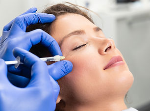 Attractive young woman is getting a rejuvenating facial injections. She is sitting calmly