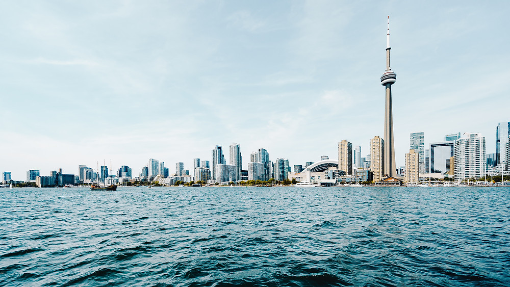 Looking across Lake Ontario and seeing Toronto's CN Tower soaring above the city's skyline while visiting Toronto