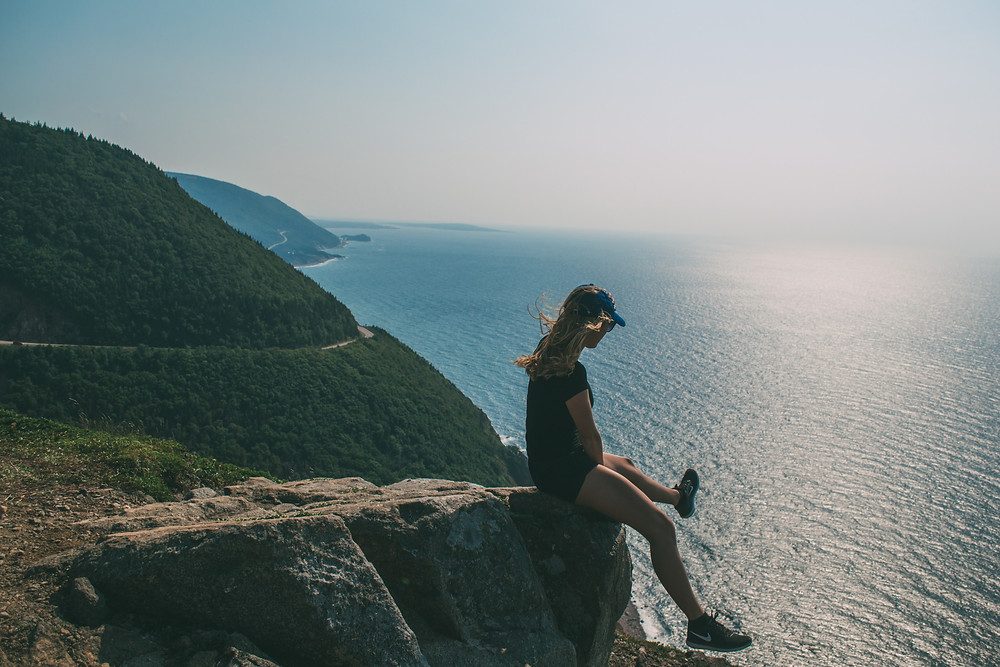 A backpacker hanging her feet off a lookout, overlooking the Atlantic Ocean as she travels around Cape Breton Island