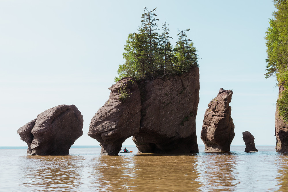A kayaker rowing through New Brunswick's Hopewell Rocks at high tide