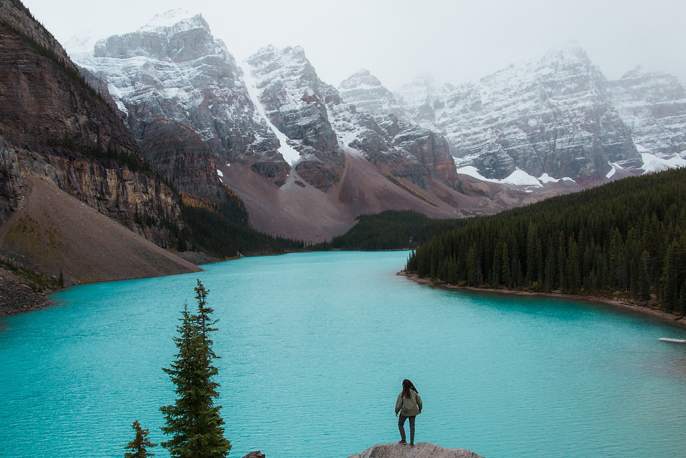 Backpacker standing in front of Moraine Lake while traveling Alberta