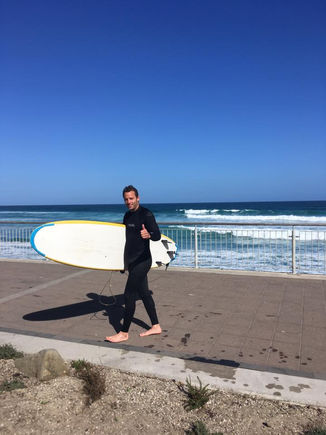 Tour Guide Connor Holding a Surf Board After a Day of Surfing in New Zealand