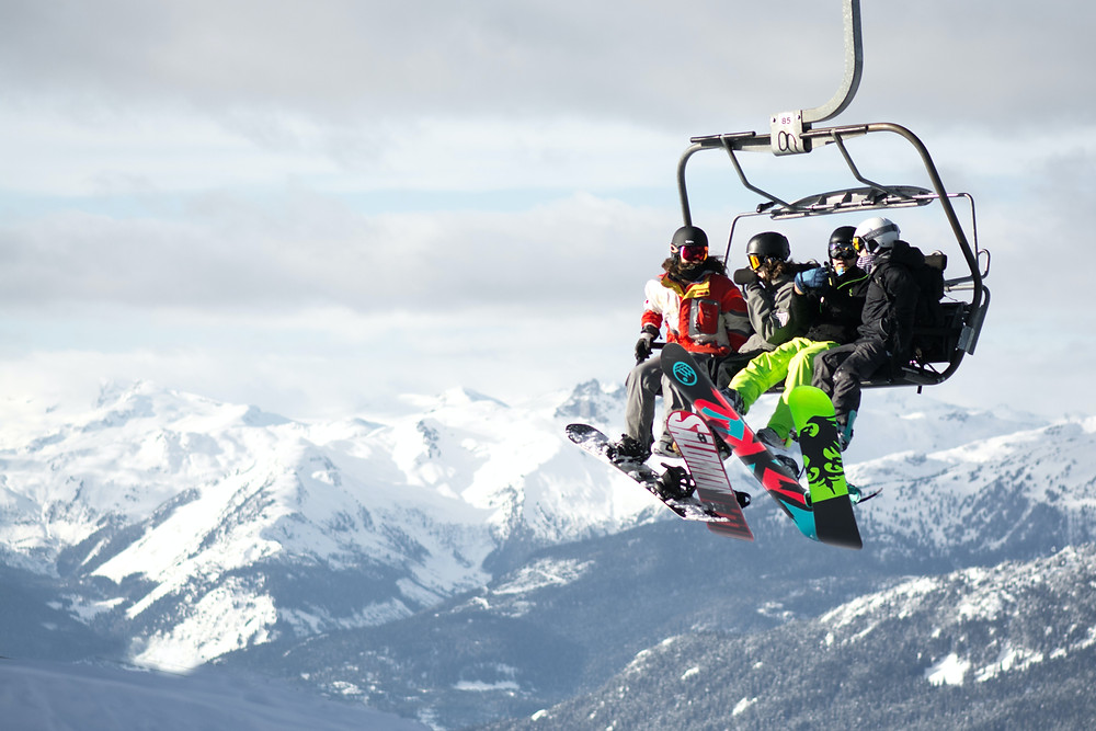 Snowboarders chatting while on a chairlift to the top of Whistler Mountain while traveling in British Columbia