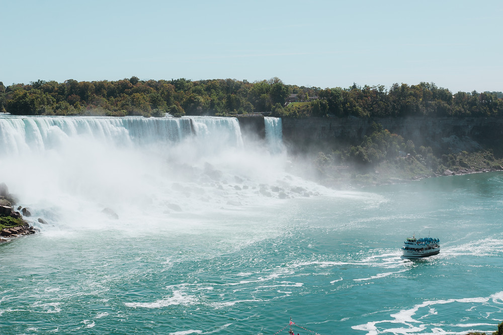 Boat cruising along the bottom of Niagara Falls where passengers traveling to Canada are being sprayed by the powerful mist