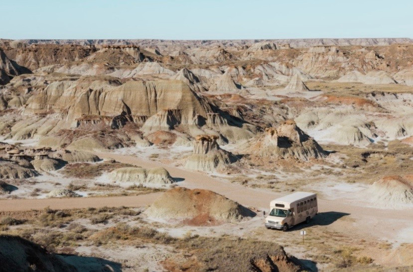 Lonely tour bus with nothing but apocalyptic badlands surrounding it