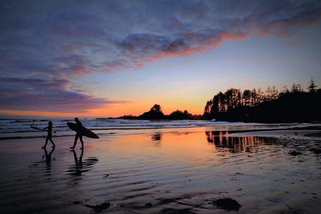 Two surfers walking along the beach at sunset while traveling Tofino