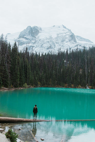 Traveller Looking At Turquoise Waters of Joffre Lake in British Columbia, with Deep Forests and Soaring Mountains in Background