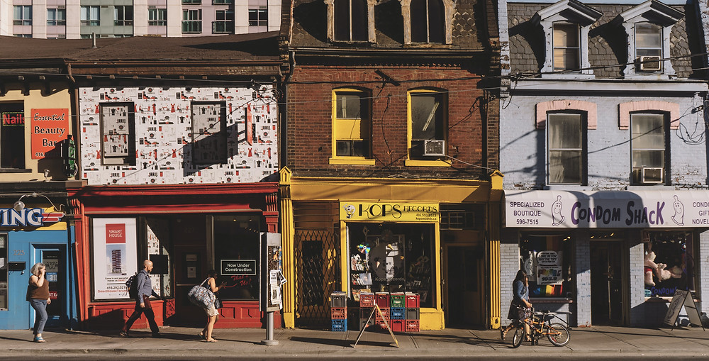 People walking in front of the quirky old streets of Toronto while traveling in Canada