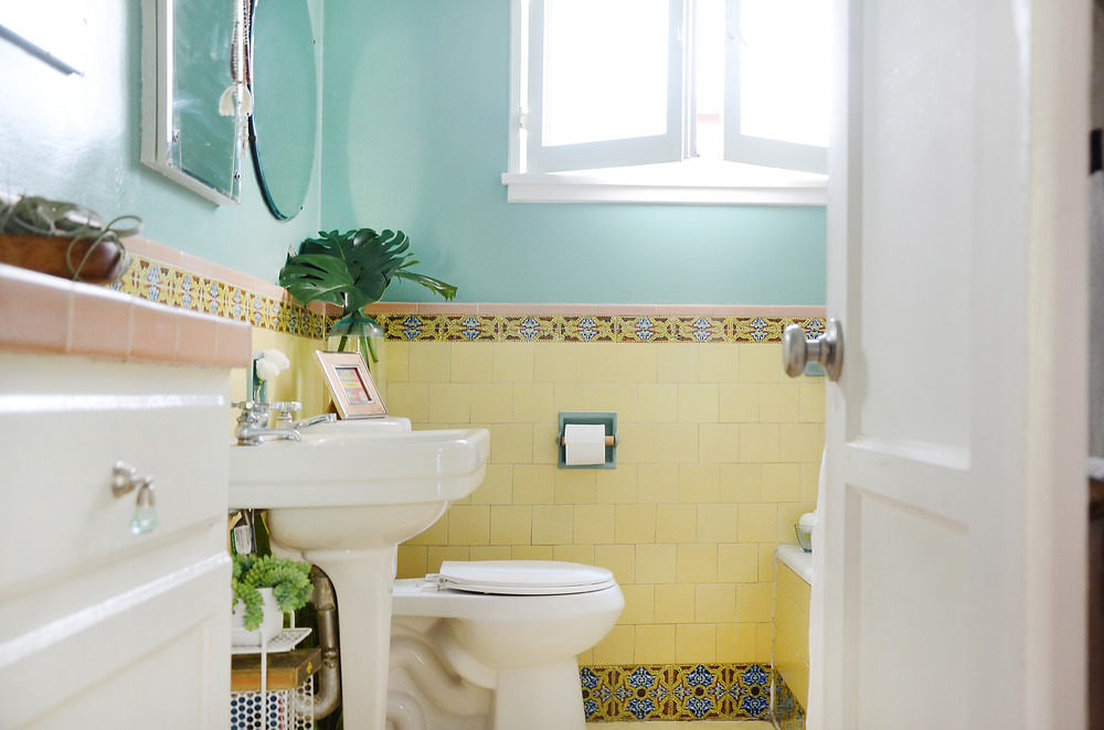 An open door reveals a small yellow bathroom. This photo is part of a blog for eConserve, a multifamily water company.
