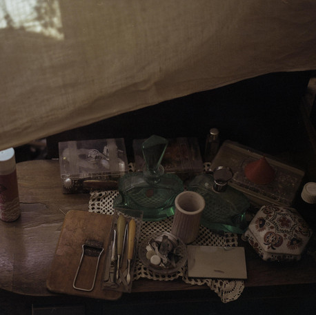 Jewellery boxes, perfume bottles, sprays, and more left on the bedside table by the bed of my great-grandmother, who passed away around thirty years ago. Everything in the flat has remained exactly the same.