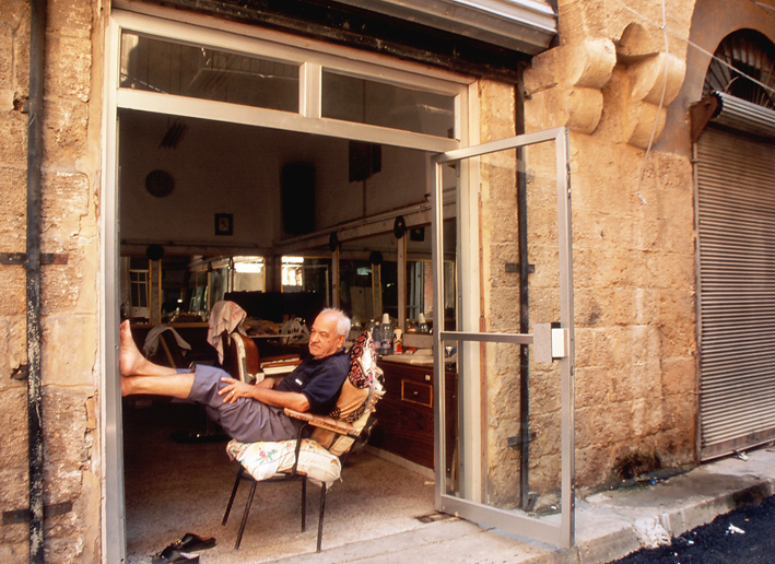 Barber relaxing outside his shop Tripoli North Lebanon