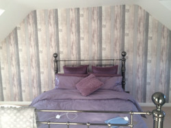 feature wall wallpapered in bedroom