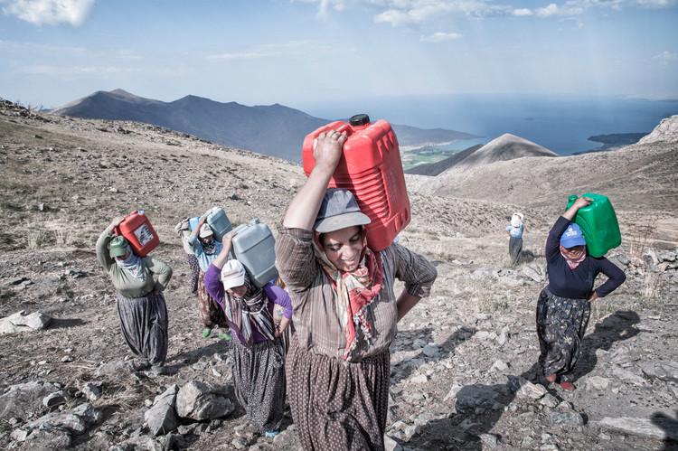 The herdswomen carry bins filled with milk. Van, Turkey. August 2011.