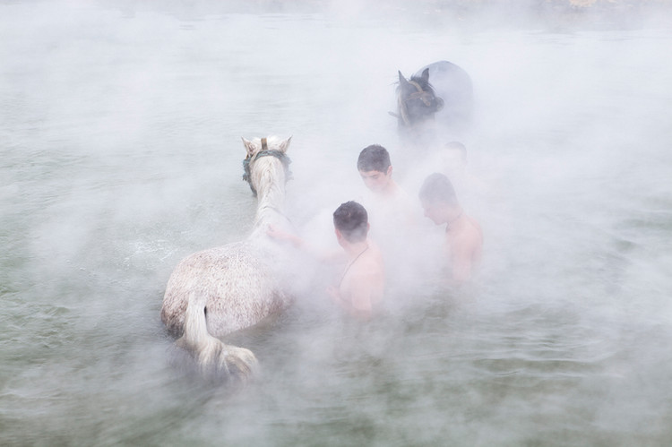 Boys clean the horses in the hot spring. February 2013.