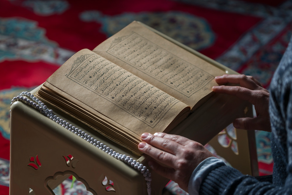 This is a picture of an open Quran resting on a podium. There are two hands resting on it, as if to keep the book open.