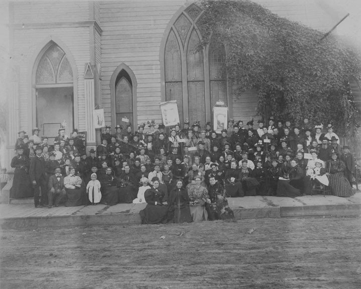 Women's Temperance League members seated outside the First Methodist Church on 6th and Bush. Inscribed on the back: From someof your friends and sisters --- to Lizzie H. Mills --- W. C. T. U. Women wear fancy hats and long high-collar dresses. Some children and men are also in the photo. A dirt road in the foreground passes by the church. Some of the women hold signs. Names are inscribed on the back, some of them too faint to read, and include: Emma Cash from Los Angeles, M. E. Stewart from Los Angeles, Charity E. Way, Sophia Webber from Riverside, Rachel Beardsley, Mrs. Ada R. Hand from Los Angeles. (It is noted that Lecil Slaback does not recognize this as a Santa Ana church.)