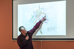 Speaker pointing to a projected map during a housing charrette.
