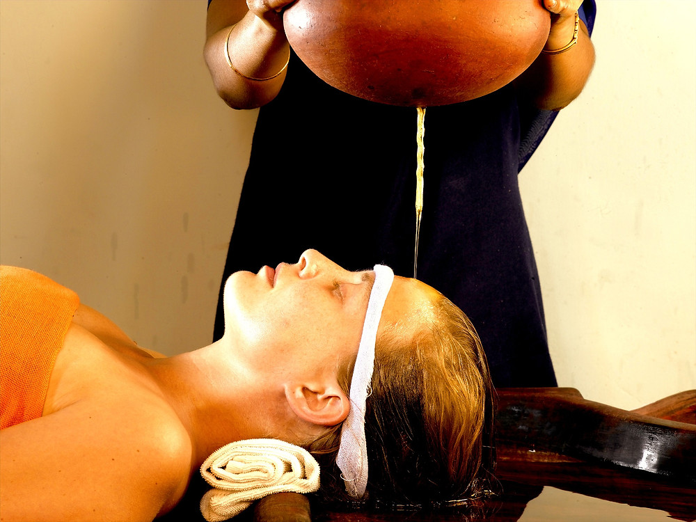 woman lying down with eyes closed with oil being dripped on her head