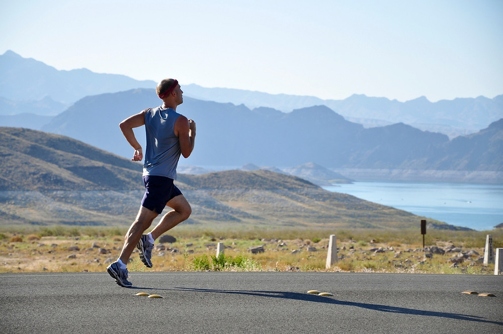 man running on road with views of lake and mountains