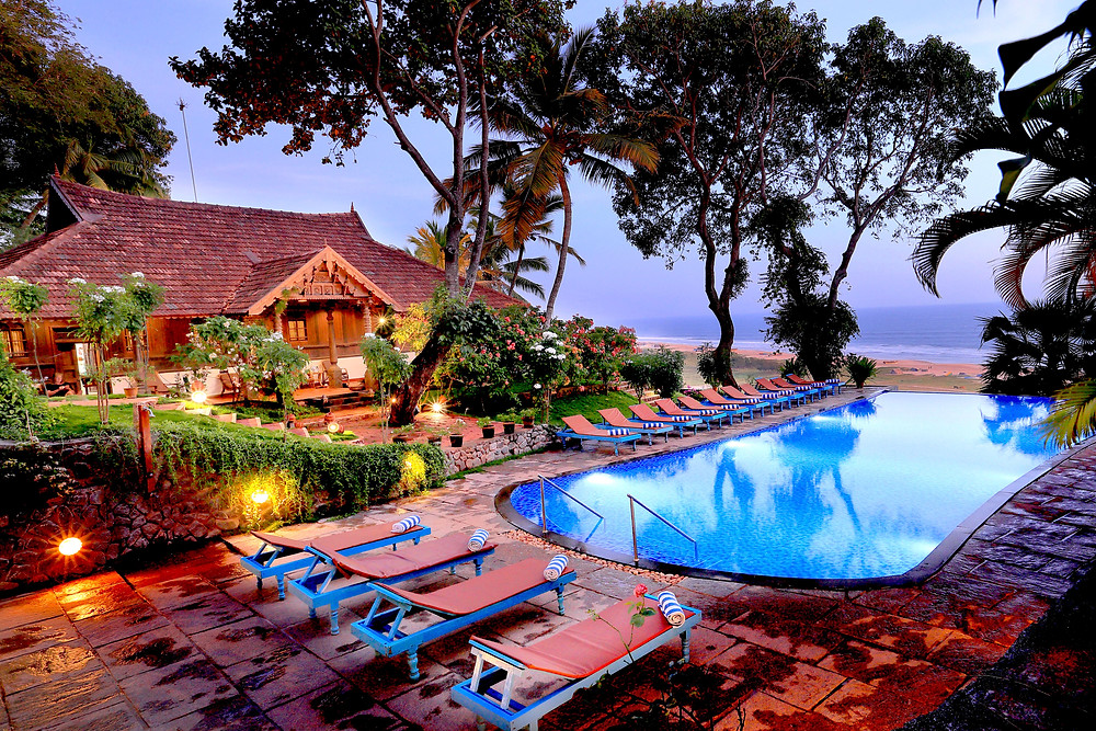 sunbeds by swimming pool overlooking sea in Kerala