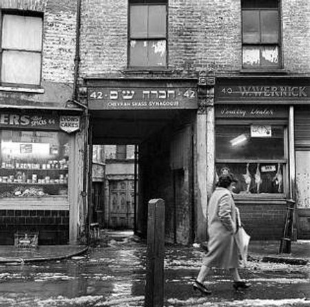 "Photo taken by John Gay. ""On a cold day a woman walks past the Chevrah Shass Synagogue, which is tucked away down an alley. The carriage archway from the street is flanked by local shops."""