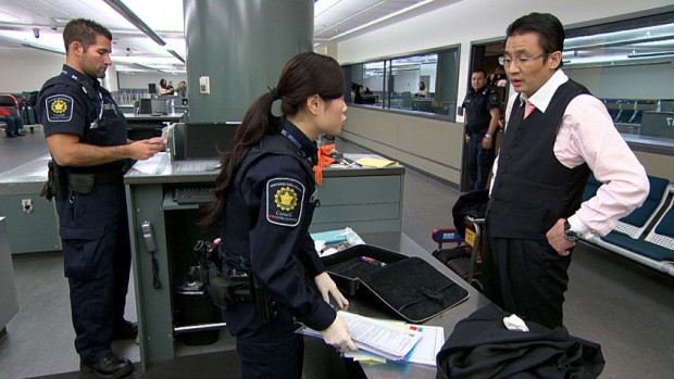 A CBSA Officer inspects a travelers bag during a secondary inspection