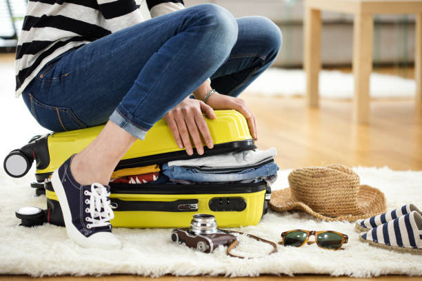 Woman struggling to close full suitcase